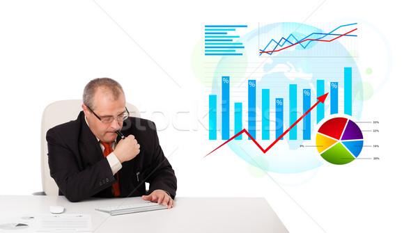 Imprenditore seduta desk statistiche isolato bianco Foto d'archivio © ra2studio