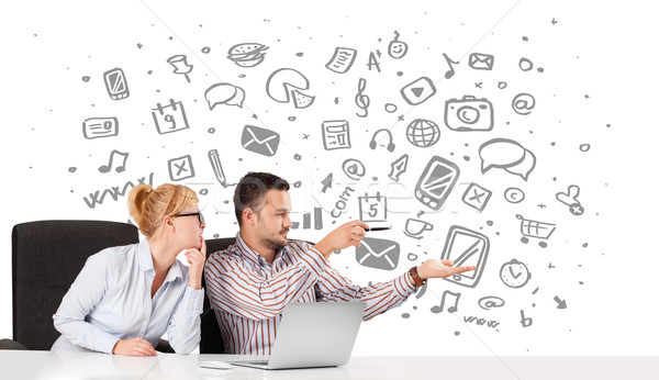 Young businessman and businesswoman with all kind of hand-drawn icons in background Stock photo © ra2studio