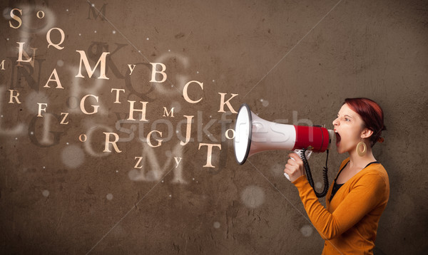 Young girl shouting into megaphone and text come out Stock photo © ra2studio