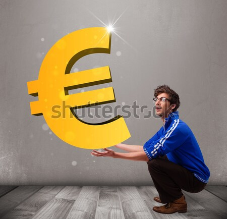 Stock photo: Good-looking boy holding a big 3d gold euro sign