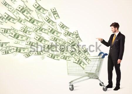 Businessman with shopping cart with dollar bills Stock photo © ra2studio