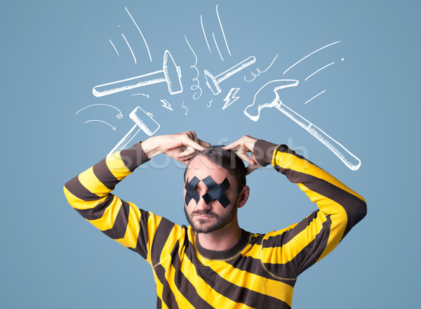 Young man with glued eye and hammer marks Stock photo © ra2studio