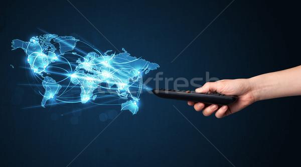 Main télécommande médias sociaux réseau social carte du monde Photo stock © ra2studio