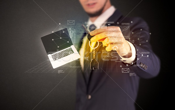 Stock photo: Businessman holding keys with graphs around