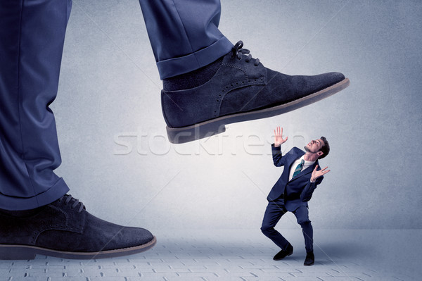 Young businessman getting crushed Stock photo © ra2studio