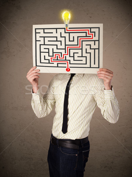 Businessman holding a paper with a labyrinth on it in front of h Stock photo © ra2studio