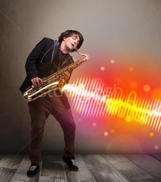 молодым человеком играет саксофон красочный звук волны Сток-фото © ra2studio