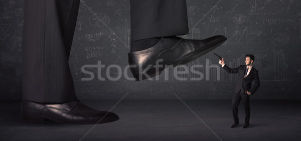 Huge leg stepping on a tiny businnessman concept Stock photo © ra2studio