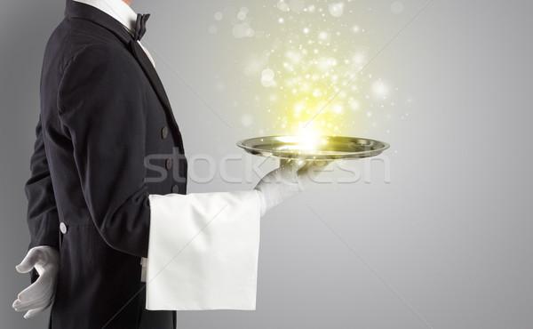 Waiter serving mysterious light on tray Stock photo © ra2studio