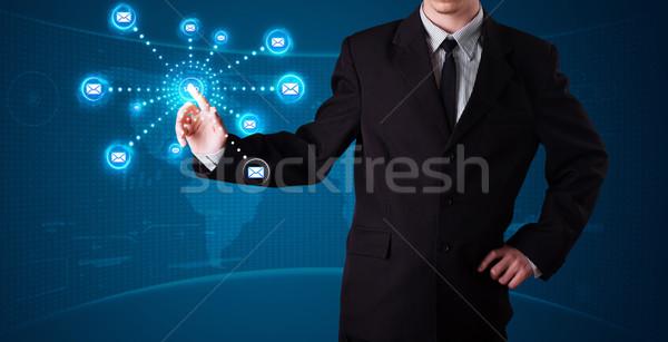 Businessman pressing virtual messaging type of icons Stock photo © ra2studio