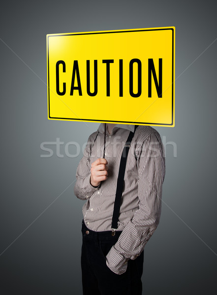 Businessman holding a caution sign Stock photo © ra2studio