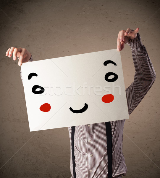 Businessman holding a cardboard with a smiley face on it Stock photo © ra2studio