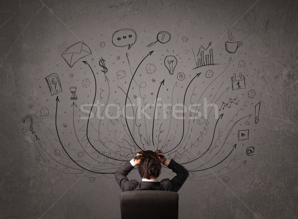 Stock photo: Businessman in front of a chalkboard deciding with arrows and si