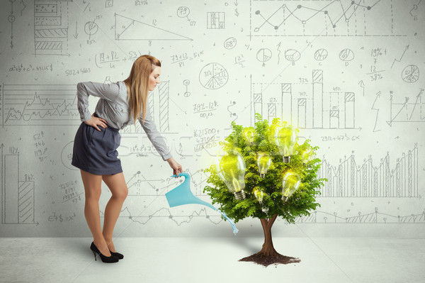 Business woman pouring water on lightbulb growing tree Stock photo © ra2studio