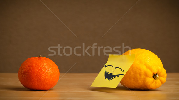 Lemon with post-it note laughing on orange Stock photo © ra2studio