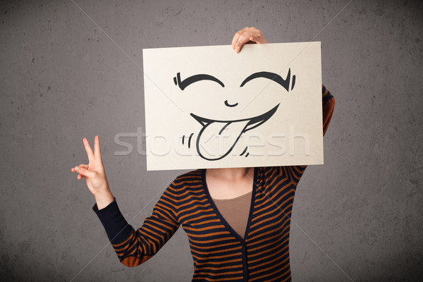 Woman holding a paper with cute smiley face on it in front of he Stock photo © ra2studio