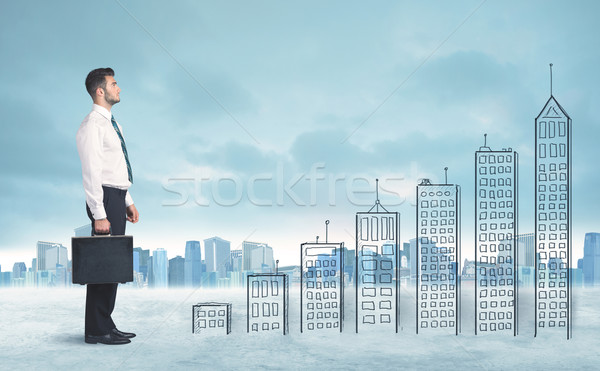 Business man climbing up on hand drawn buildings in city Stock photo © ra2studio