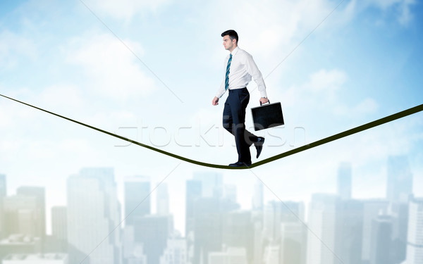 Salesman walking on rope above the city Stock photo © ra2studio