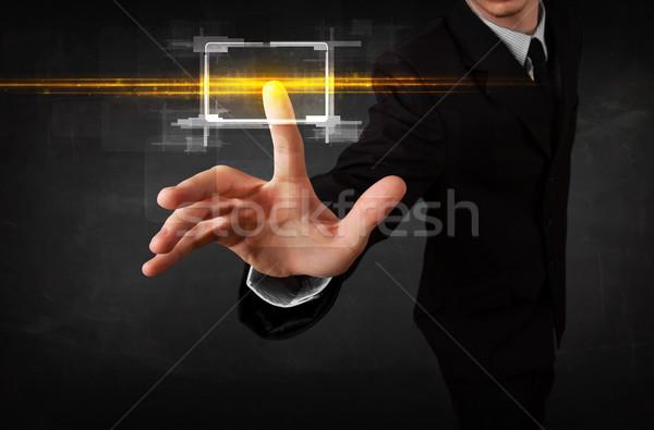 Tech business person touching button with orange light beams con Stock photo © ra2studio