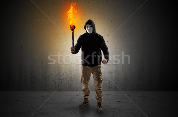 Man walking in an empty space with burning flambeau Stock photo © ra2studio