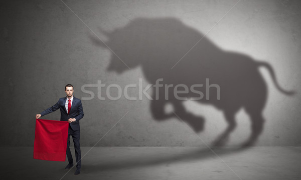 Businessman with bull shadow and toreador concept Stock photo © ra2studio