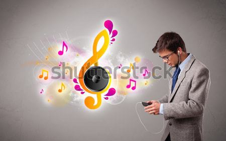 young man singing and listening to music with musical notes  Stock photo © ra2studio
