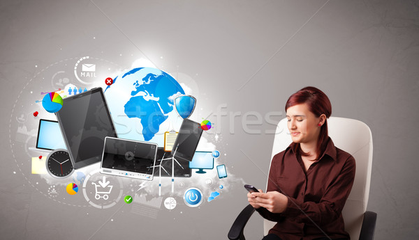 young woman sitting and browsing on her phone Stock photo © ra2studio