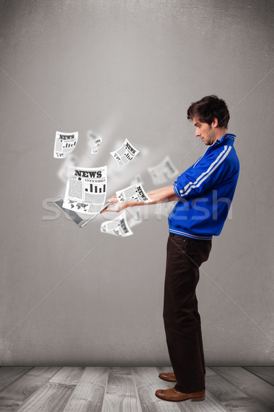 Young man holding a laptop and reading the explosive news Stock photo © ra2studio