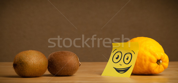 Stock photo: Lemon with post-it note watching at kiwis