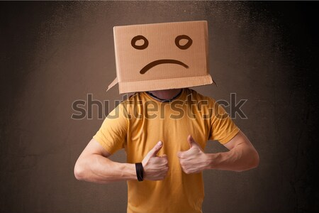 Young man with a brown cardboard box on his head with sad face Stock photo © ra2studio