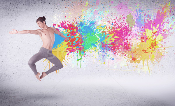 Stock photo: Modern street dancer jumping with colorful paint splashes