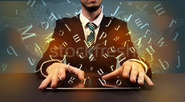 Man typing in formal clothing and letters around Stock photo © ra2studio