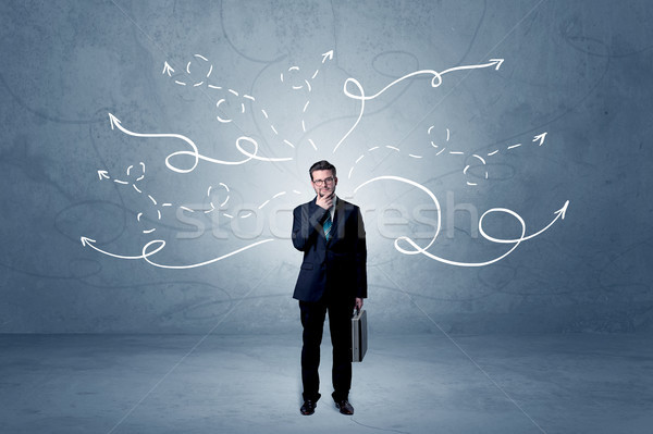 Businessman standing with winding arrows around Stock photo © ra2studio