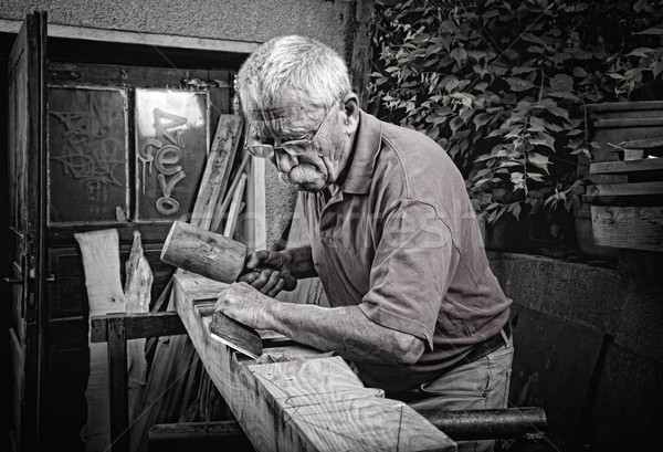 Old woodcarver working with mallet Stock photo © ra2studio