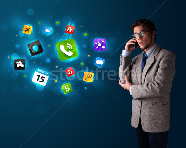 Young man calling by phone with various icons Stock photo © ra2studio