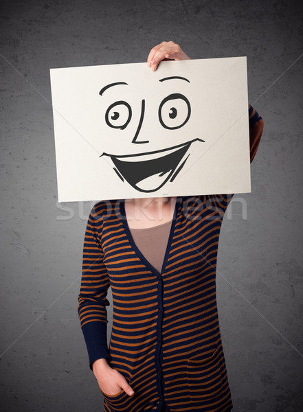 Woman holding a cardboard with smiley face on it in front of her Stock photo © ra2studio