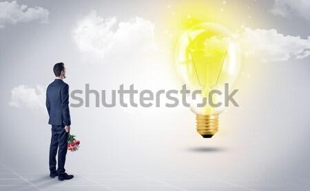Businesswoman on rock mountain with idea bulb Stock photo © ra2studio