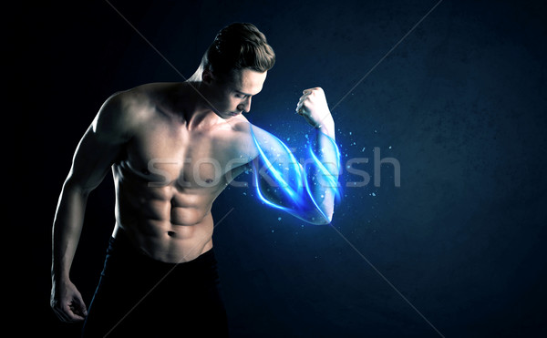 Fit athlete lifting weight with blue muscle light concept Stock photo © ra2studio