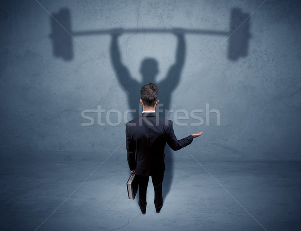 Businessman with weight lifting shadow Stock photo © ra2studio