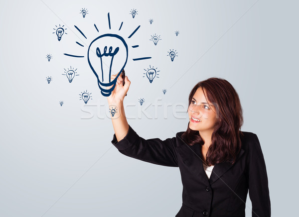 Woman drawing light bulb on whiteboard Stock photo © ra2studio