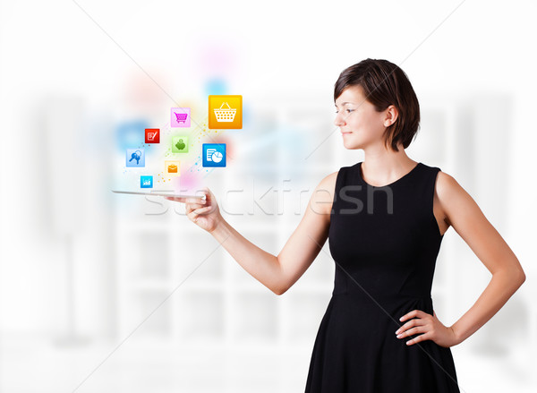 Young woman looking at modern tablet with colourful icons Stock photo © ra2studio