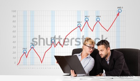 Young businessman and businesswoman calculating stock market with rising graph in the background Stock photo © ra2studio