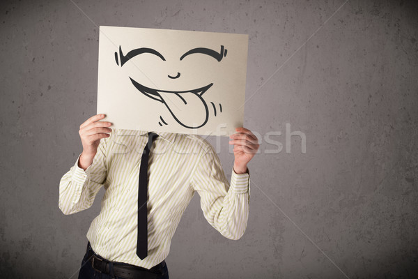 Businessman holding a paper with funny smiley face in front of h Stock photo © ra2studio