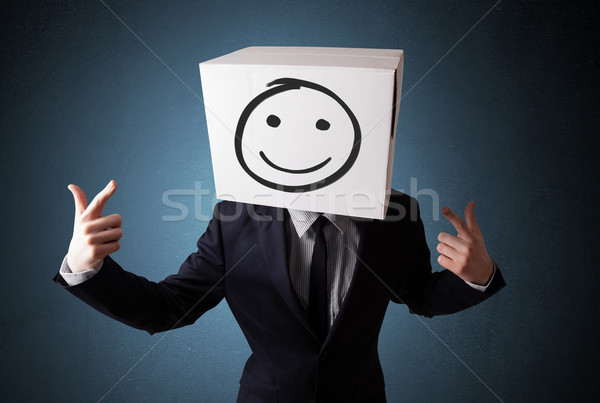 Businessman gesturing with a cardboard box on his head with smil Stock photo © ra2studio
