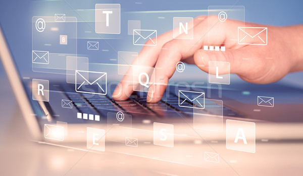Hand typing on keyboard with digital tech icons Stock photo © ra2studio