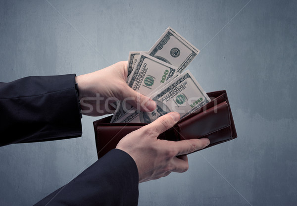 Hand in suit takes out dollar from wallet Stock photo © ra2studio