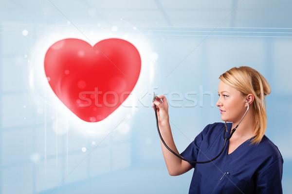 Young nurse healing a red heart Stock photo © ra2studio