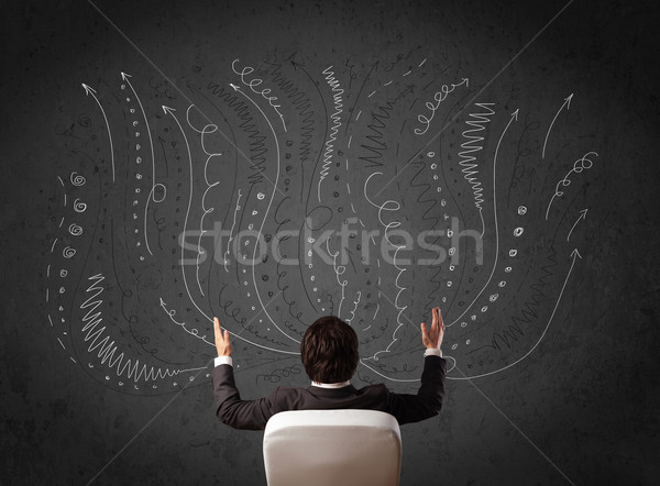Businessman thinking with sketched arrows in front of a chalkboa Stock photo © ra2studio
