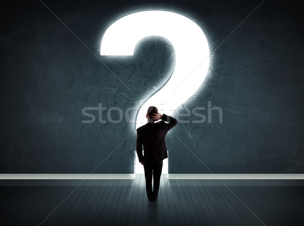 Business man looking at wall with a bright question mark  Stock photo © ra2studio