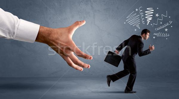 Stressful businessman running from a big hand  Stock photo © ra2studio